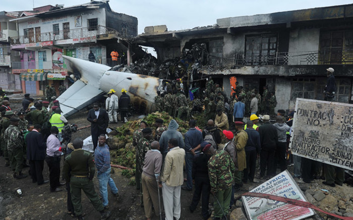 Rescuers and onlookers look at the wreckage of a cargo plane which crashed at a commercial building in a Nairobi suburb shortly after takeoff on 2 July, 2014 from the Kenyan capital's main airport, the busiest in east African. Picture: AFP.