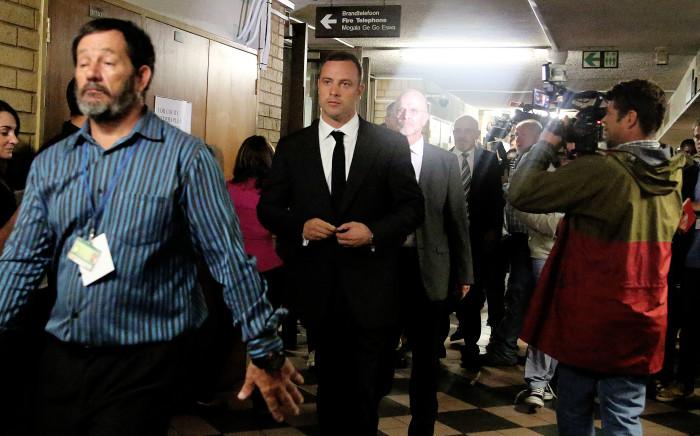 Oscar Pistorius is escorted into the Pretoria High Court ahead his trial for murder. Picture: Sebabatso Mosamo/EWN.