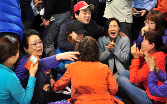 South Korean relatives of passengers on board a capsized ferry cry as they wait for news about their loved ones, at a gym in Jindo on 17 April, 2014. Picture: AFP.