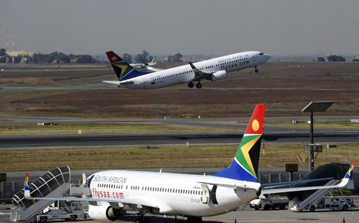 FILE: A South African Airways flight takes off as another one is parked in a bay on the tarmac on 25 May, 2010 at the Johannesburg O.R Tambo International airport in Johannesburg, South Africa. Picture: AFP