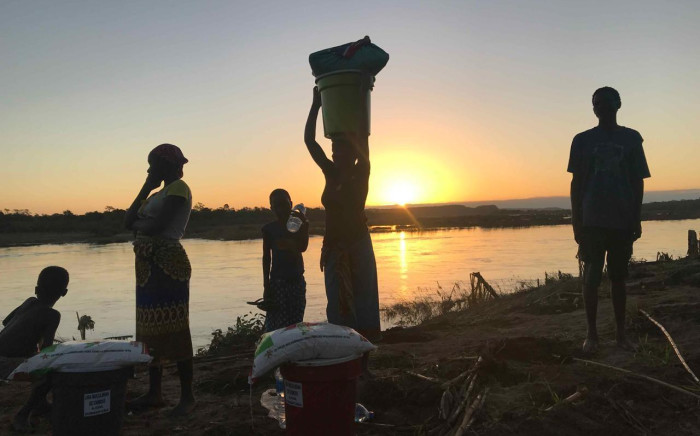 Villagers make their way back home after receiving food and water from relief workers after Cyclone Idai hit Mozambique. Picture: Christa Eybers/EWN