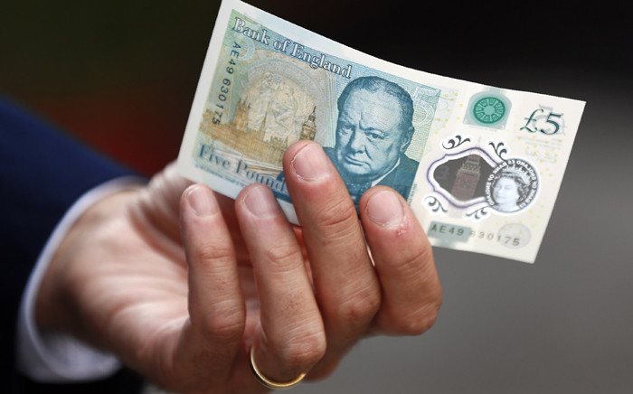 """Governor of the Bank of England Mark Carney poses with a new polymer £5 note, at Whitecross Street Market, to promote the launch of the new bank note, in London, on September 13, 2016. The Bank of England will initially issue 440 million of the new polymer £5 notes ($6.7, 5.9 euros) and the old note will cease to be legal tender in May 2017. """"We expect polymer notes to last at least two-and-a-half times longer than the current generation of fivers and therefore reduce future costs of production,"""" Carney said. STEFAN WERMUTH / POOL / AFP"""