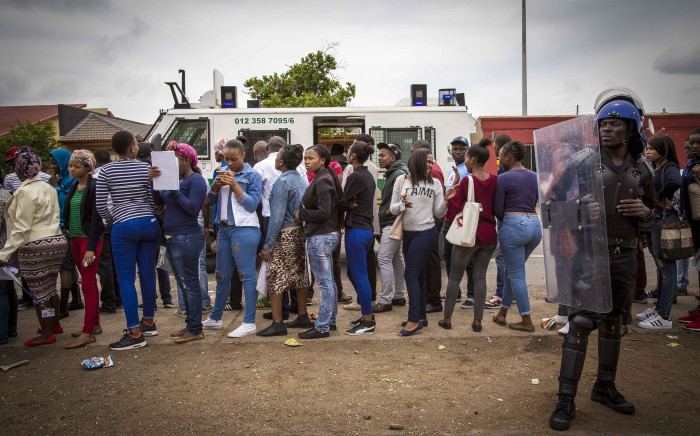 Students wait for buses to take them to their exam venue under watch of private security and police after protests at the TUT Soshanguve campus. Picture: Thomas Holder/EWN