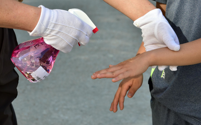 A South Korean school worker sprays sanitizer on hands of students to protect against possible MERS virus at an elementary school in Seoul on June 3, 2015. South Korea on June 2 reported its first deaths from an outbreak of the MERS virus that has infected 25 people, caused widespread alarm and triggered a closer watch by Asian neighbours on Korean arrivals.  Picture: AFP