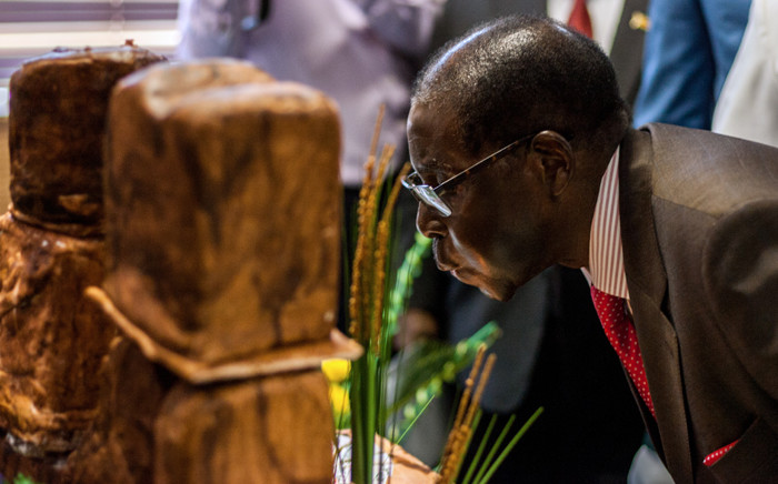 FILE: Zimbabwe's President Robert Mugabe blows out candles during a private ceremony to celebrate his 93rd birthday on 21 February, 2017 in Harare. Picture: AFP.