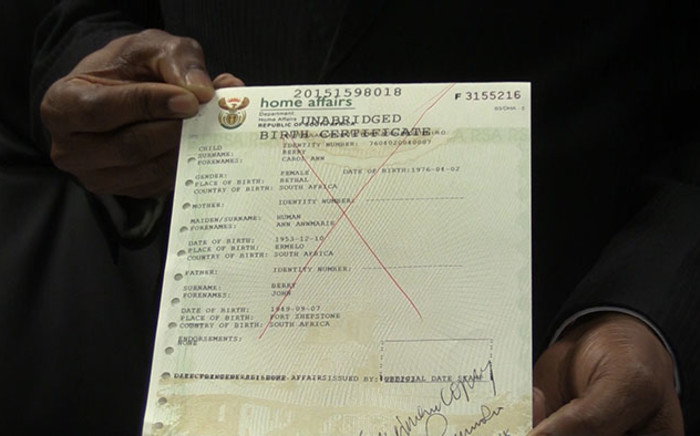 Home Affairs Director General holds up a sample of an SA unabridged birth certificate, Picture: Vumani Mkhize/EWN.