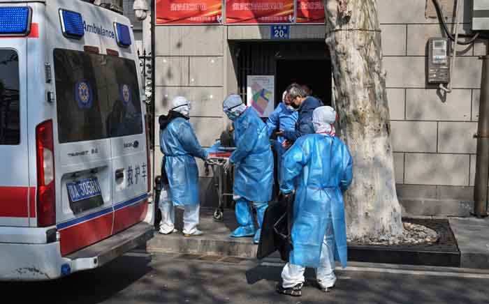 Medical staff in protective clothes are seen carrying a patient from an apartment suspected of having the virus in Wuhan, in Hubei province on 30 January 2020. Picture: AFP