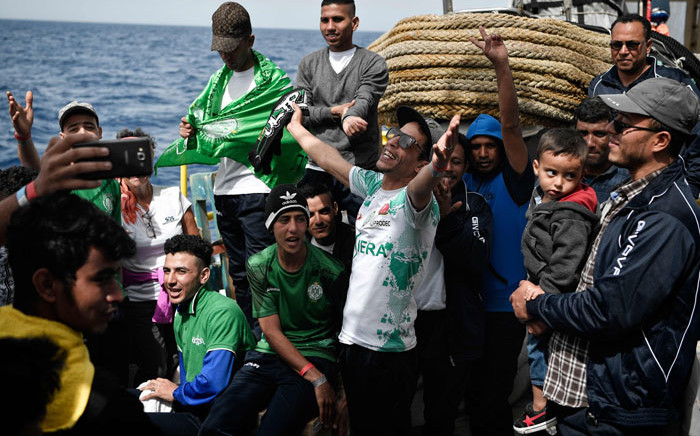 FILE: Moroccan migrants sing on a boat after being rescued at sea. Picture: AFP