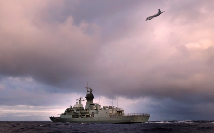 A photo shows HMAS Perth transiting through the Southern Indian Ocean as an Orion P-3K of the Royal New Zealand Air Force searches for debris for missing Malaysia Airlines flight MH 370 in the southern Indian Ocean. Picture: AFP.