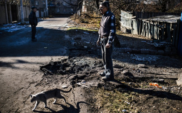 FILE: A man stands next a crater following shelling in the Kuybeshevski area in Donetsk. Picture: AFP