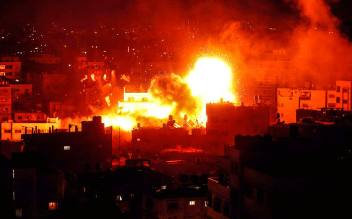 A picture taken on 12 November, 2018, shows a ball of fire above the building housing the Hamas-run television station al-Aqsa TV in the Gaza Strip during an Israeli air strike. Picture: AFP