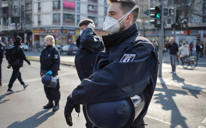 Police officers wear face masks as they surround a spontaneous rally in Berlin's Kreuzberg district on 28 March 2020, amid the novel coronavirus Covid-19 pandemic. Picture: AFP