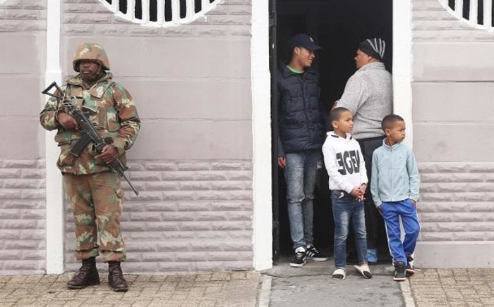 SANDF soldier on patrol in Manenberg, as a Manenberg family watch. The military has released their soldiers to help stabilise gang hot-spots, while law enforcement agencies conducted raids in the area. Picture: Bertram Malgas/EWN