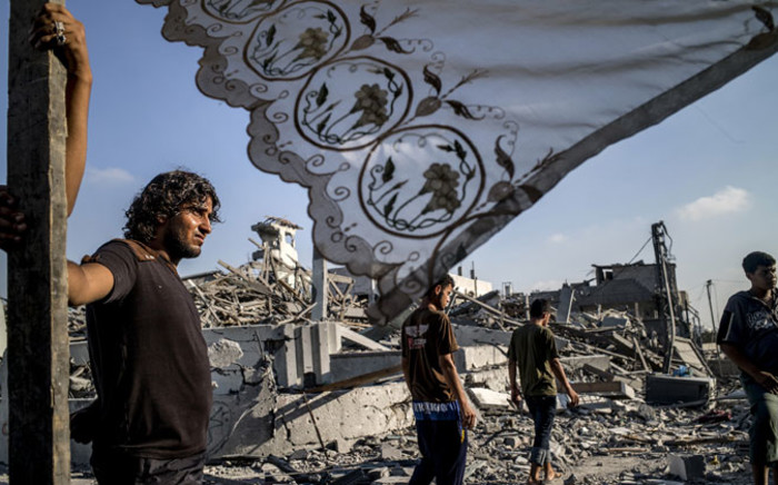 Palestinians stand next to a makeshift shelter erected outside their destroyed house in the devastated neighbourhood of Shejaiya in Gaza City on 6 August, 2014. Picture: AFP.