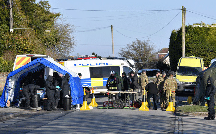 FILE: Members of the emergency services, wearing protective coveralls and breathing equipment, work alongside members of the British Army as a vehicle is loaded onto the back of a British Army lorry amid investigations in connection with a nerve agent attack in the city on 4 March. Picture: AFP