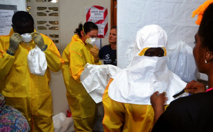 FILE:A picture taken on 24 July 2014 shows staff of the Christian charity Samaritan's Purse putting on protective gear in the ELWA hospital in the Liberian capital Monrovia. Picture: AFP
