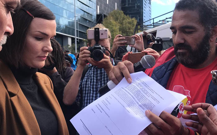FILE: A member of the Water Crisis Coalition hands over a memorandum to a City of Cape Town official on 25 April 2018. Picture: Kaylynn Palm/EWN.