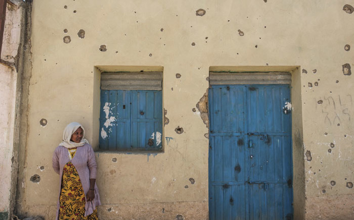 A woman leans on the wall of a damaged house which was shelled as federal-aligned forces entered the city, in Wukro, north of Mekele, on 1 March 2021. Picture: Eduardo Soteras/AFP