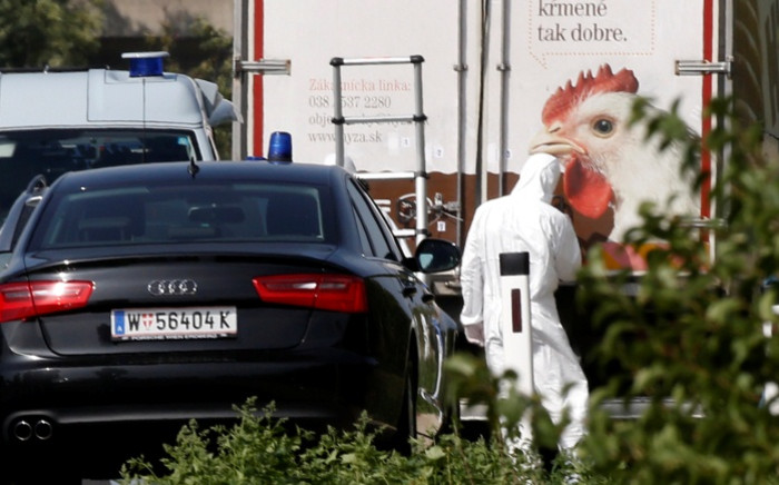 A forensic investigator is seen working on a refrigerated truck parked along a highway near Neusiedl am See, Austria, on 27 August 2015. The bodies of about 70 migrants were found in the truck on the A4 highway. Picture: AFP.