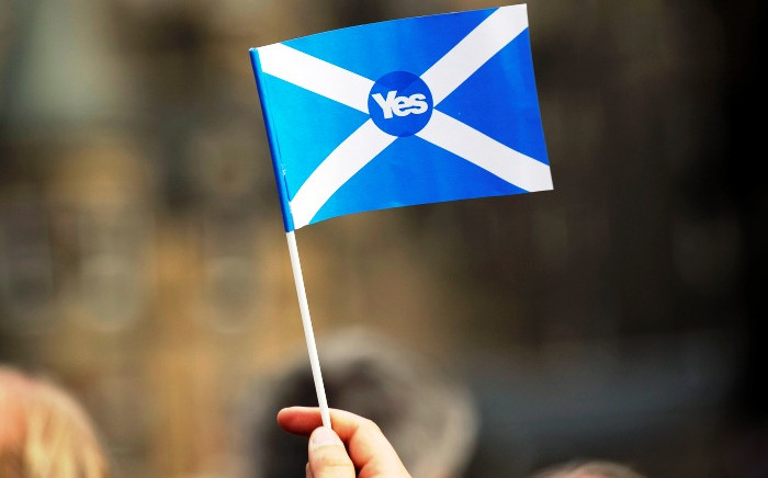 """FILE: A pro-independence supporter holds a """"Yes"""" flag as Scottish MP Jim Murphy addresses pro-union """"Better Together"""" campaign supporters in Edinburgh on 8 September, 2014. Picture: AFP."""