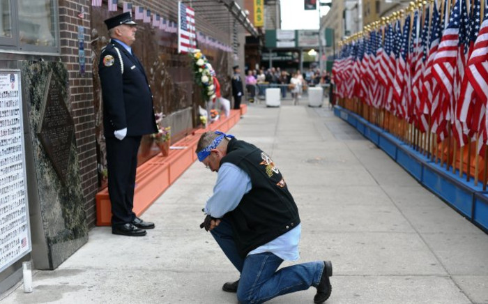 People pay their respects at the at the Fire Department of New York (FDNY) Memorial Wall Located at FDNY Engine and Ladder 10 on September 11, 2014 on the 13th anniversary of the September 11, 2001 attacks. AFP.