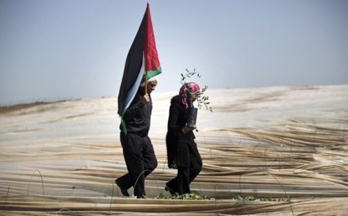 A man holding a Palestinian flag and a woman carrying an olive tree on Land Day during which people plant olive trees near the Israeli border in Jabalia, in the northern Gaza Strip. Picture: AFP.