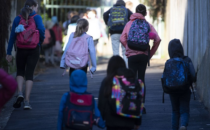 School children make their way to school after the government allowed schools to re-open under Level 2 guidelines in Wellington on 18 May 2020. Picture: AFP