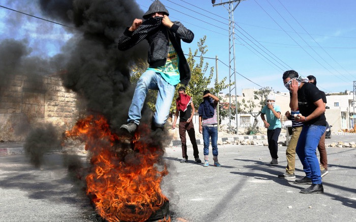 Palestinians stand around a burning tyre during clashes with Israeli soldiers in the West Bank village of Seir, near Hebron, 11 November 2014. Meanwhile, two Palestinians stabbed and killed two Israelis in separate attacks in Tel Aviv and the West Bank, police said, amid heightened Israeli-Palestinian tensions. Picture: EPA/ABED AL HASHLAMOUN.