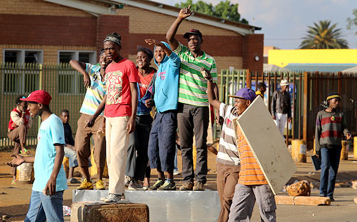 Residents of Bekkersdal in Westonaria at a stand-off with police during a service dilevery protest on 24 October 2013. Picture: Sebabatso Mosamo/EWN