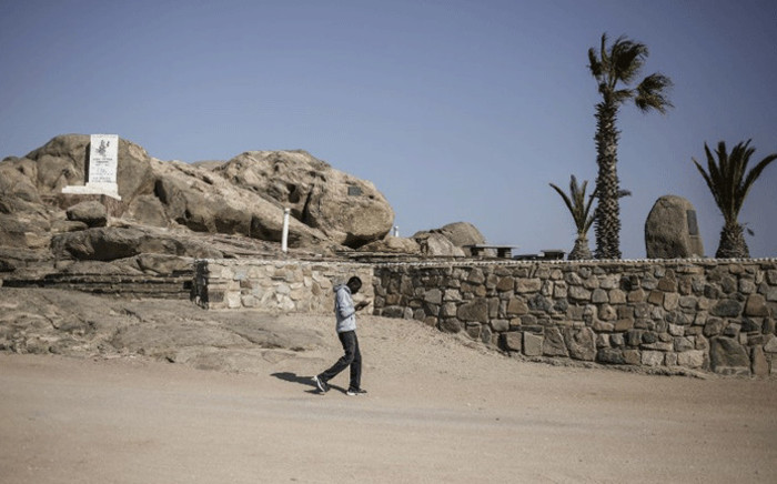 FILE: A man looks at his phone as he walks by a monument remembering the alleged genocide committed by German forces against Herero and Nama people in 1904, at Shark Island former concentration camp on 26 June, 2017 in Luderitz, Namibia. Picture: AFP