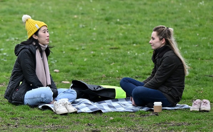 People sit on the grass together chatting in Battersea Park in London on March 28, 2021. From Monday, England's stay-at-home order to combat the spread of the coronavirus will be relaxed to enable groups of up to six people to meet outside. The government plans to allow outdoors drinking in pub gardens, and non-essential retail such as hairdressers, from April 12. Picture: Justin Tallis / AFP.