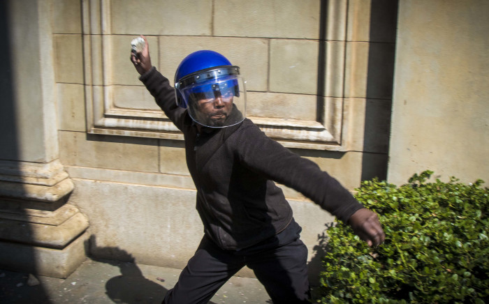 A member of the private security tasked to block students from entering Senate House on Wits University campus picks up a brick to throw back at protesting students. Picture: Thomas Holder/EWN