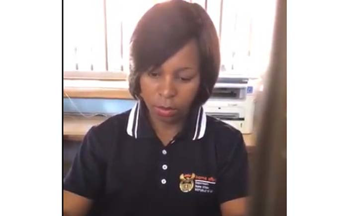 A screengrab of the Home Affairs employee who was distracted by her phone and stamped a passport twice.