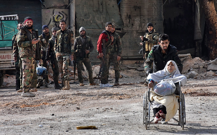 A member of the government forces pushes an injured woman in a wheelchair as civilians are evacuated from Aleppo's al-Shaar neighbourhood after government forces took control of the area in the eastern part of the northern Syrian city on 7 December, 2016. Picture: AFP.
