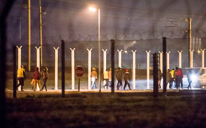 Security agents escort migrants after their intrusion in the Eurotunnel site in Coquelles, northern France, on 3 October, 2015. Picture: AFP.