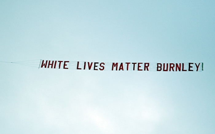 A plane towing a banner reading 'White Lives Matter Burnley' is seen in the sky above the stadium during the English Premier League football match between Manchester City and Burnley at the Etihad Stadium in Manchester on June 22, 2020. Michael Regan/AFP