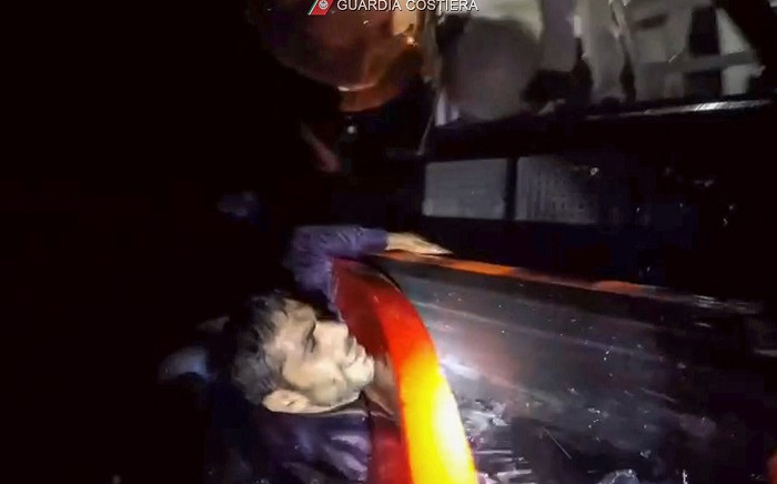 FILE: This image grabbed from a video taken on November 14, 2020 off the island of Lampedusa and handout on November 15, 2020 by the Italian Coast Guards (Guardia Costiera), shows a migrant clinging to a patrol boat of the Italian Coast Guards during a rescue operation after the capsizing of the migrants' boat. Picture: AFP.