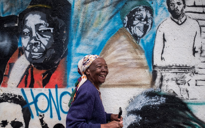 Busi Mildred Hlatshwayo, who works at the Soweto Kliptown Youth Centre (SKY), is photographed next to a wall bearing a mural on 5 April 2019 in Kliptown near Soweto. Picture: AFP
