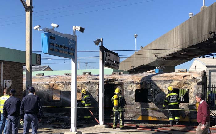 Firefighters contain a fire that left one train carriage damaged at Koeberg Train Station, Cape Town. Picture: Bertram Malgas/EWN