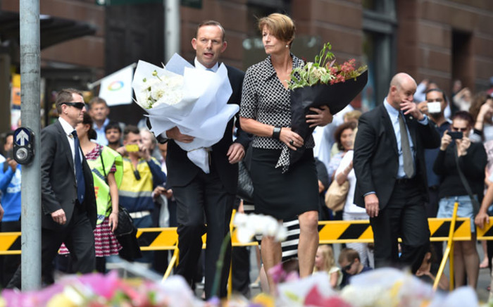 FILE: Australian Prime Minister Tony Abbott and his wife Margaret prepare to lay wreaths at a makeshift memorial near the scene of a fatal siege in the heart of Sydney's financial district on 16 December, 2014. Picture: AFP.