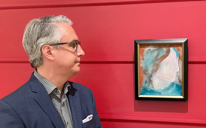 A handout photo released on June 15, 2021, courtesy of the auction house Cowley Abbott shows Canadian Art Specialist Rob Cowley looking at a painting by British pop icon David Bowie in Toronto, Canada. Handout / Cowley Abbott / AFP