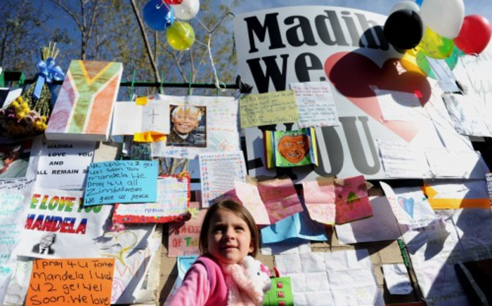 A little girl is seen among messages of hope put up on a wall outside the Medi-Clinic Heart Hospital where a critically-ill  Nelson Mandela is being treated, Thursday, 27 June 2013.Support for Mandela was growing  with well-wishers of different nationalities visiting the hospital in Pretoria.The presidency has said that his condition remains critical. Picture: Werner Beukes/SAPA