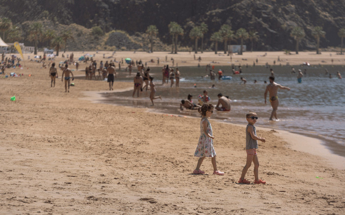 People sunbathe at Las Teresitas beach in the Spanish Canry Island of Tenerife on May 25, 2020, on the first day after beaches reopened in parts of the country after months-long closures. Picture: AFP.