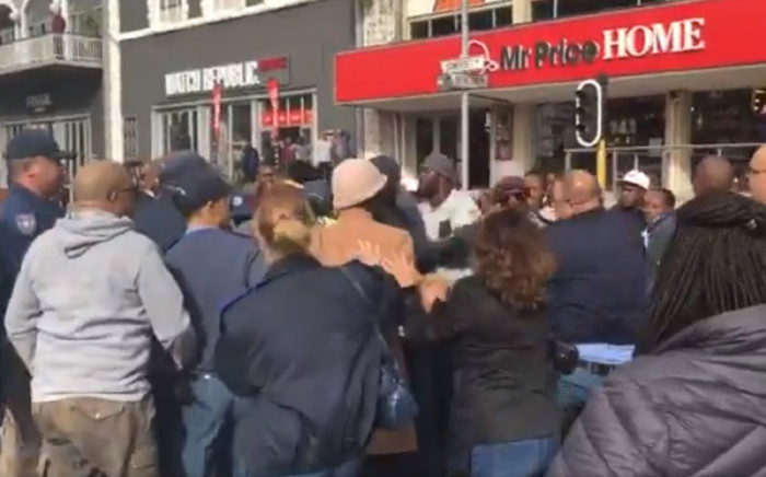 A screengrab of Uber and Taxify drivers scuffling with traffic police during a protest in Somerset Road, Cape Town on 26 June 2018.