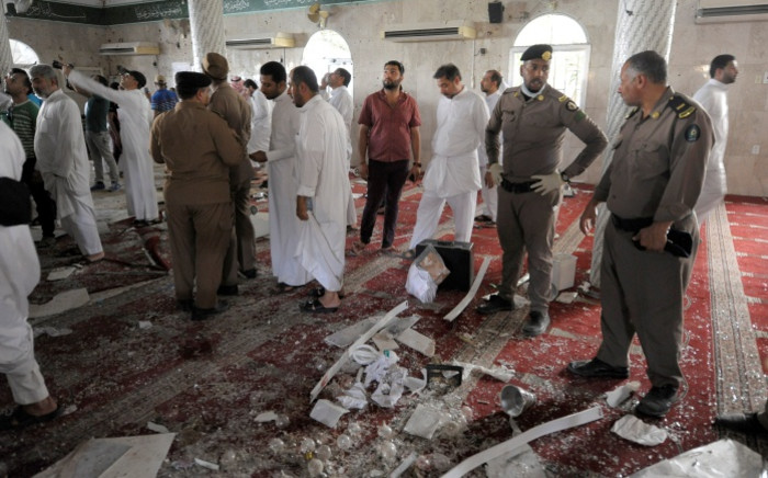 Saudi policemen gather around debris following a blast inside a mosque, in the mainly Shi'ite Saudi Gulf coastal town of Qatif, 400 km east of Riyadh, on May 22, 2015. Picture: AFP.""
