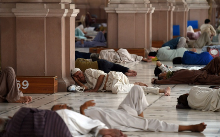 Pakistani Muslims rest at a mosque during a heatwave in Karachi on 22 June 2015. Picture: AFP.