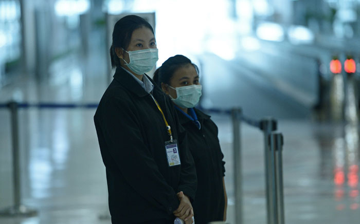 FILE: Airports of Thailand employees wear face masks as they wait for travelers to walk past a thermoscan checking their body temperature on arrival at Bangkok's Suvarnabhumi Airport on 19 June, 2015. Picture: AFP.