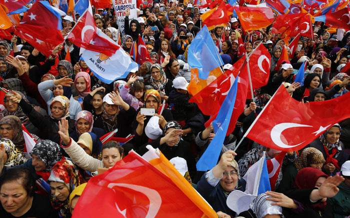 Supporters of the ruling Justice and Development Party (AKP) cheer and wave the Turkish national flag and the party's flag as they wait for the arrival of Turkey's Prime Minister and Justice and Development (AK) party leader Ahmet Davutoglu to address an election rally in Ankara, on 31 October 2015. Picture: AFP