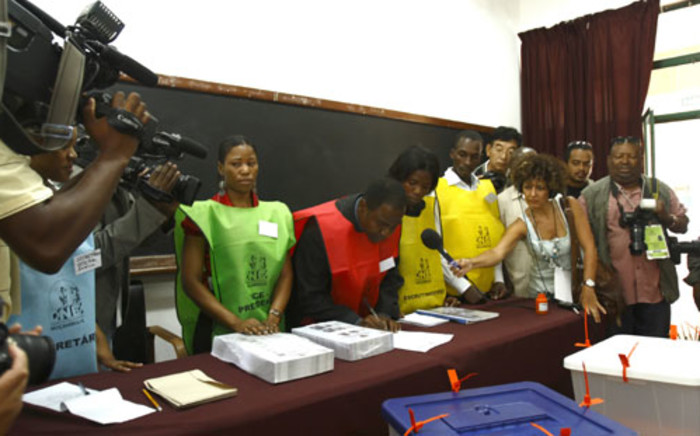 FILE: A municipal employee, flanked by other workers, signs documents during the fourth Mozambican general elections in Maputo on 28 October 2009. Picture: AFP