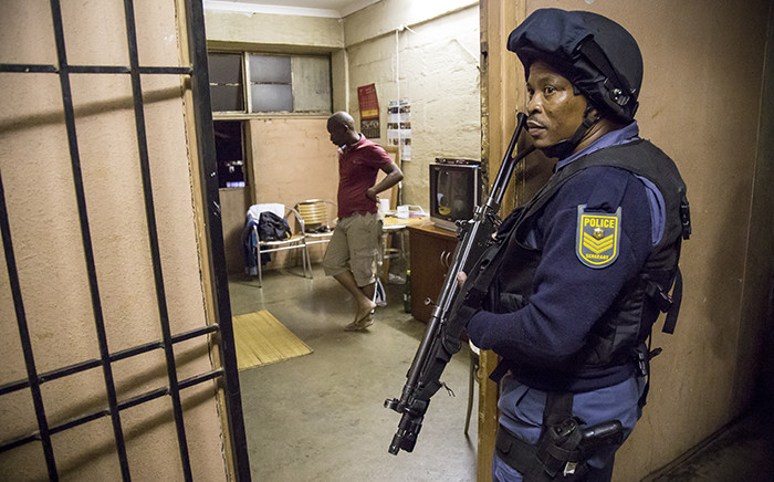 After a search, police move out of a room where a couple are living in Alexander during the overnight raid on 22 April 2015. Picture: Thomas Holder/EWN.